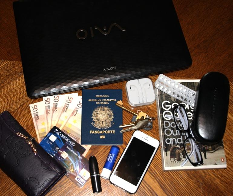 O básico na mala de mão: passaporte, dinheiro e livro para distrair durante o voo.